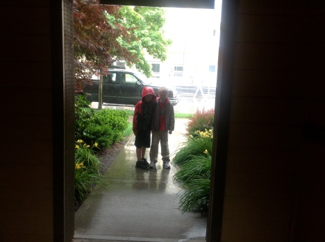 We walked back through the apartment hallways. But they went out to stand in the rain anyway.
